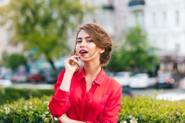 Крупным планом горизонтальный портрет красивой девушки с красивой прической, стоя в парке. она носит красную блузку. она смотрит в камеру. Бесплатные Фотографии