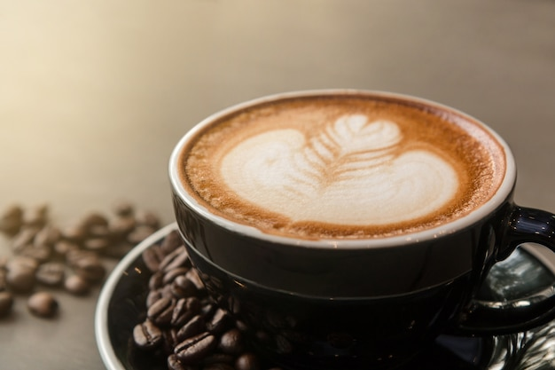 Close-up of hot latte coffee with latte art in a black cup. Premium Photo