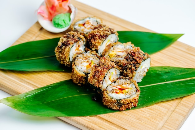 Close up of hot sushi rolls served with ginger and wasabi on wood board Free Photo