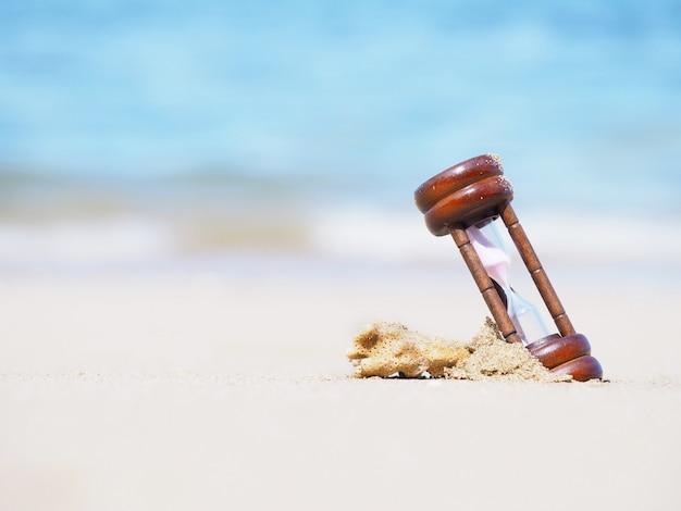 Close up hourglass on summer beach. Premium Photo
