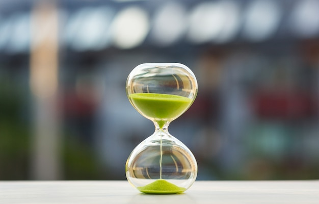 Close-up, hourglass with green sand on a blurred background Premium Photo