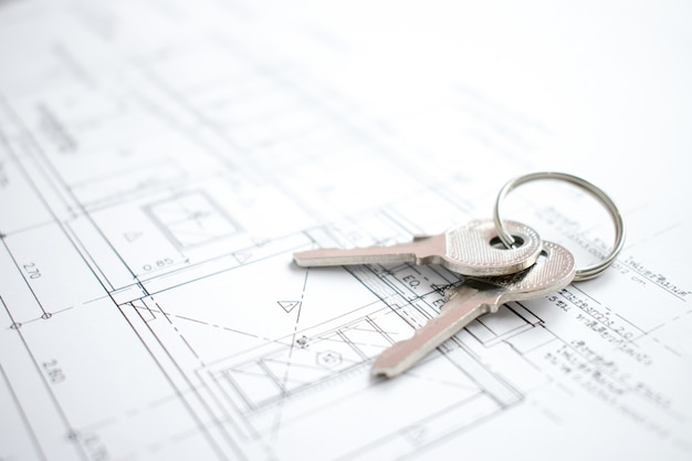 Close-up of house keys  on blueprint paper of new home. Premium Photo