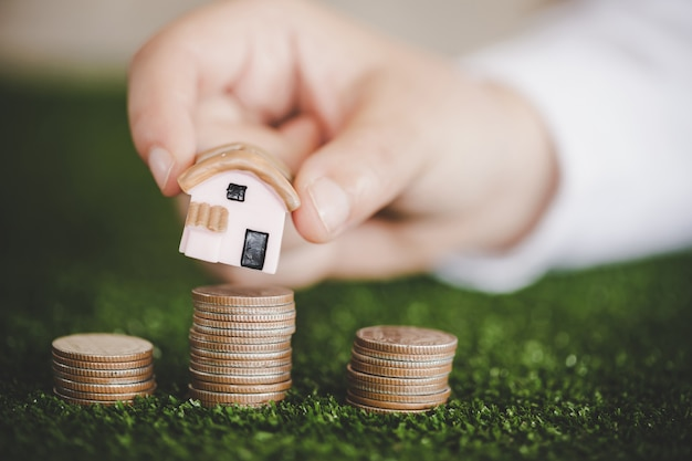 Close-up of a house models placed on top of stacked coins Premium Photo