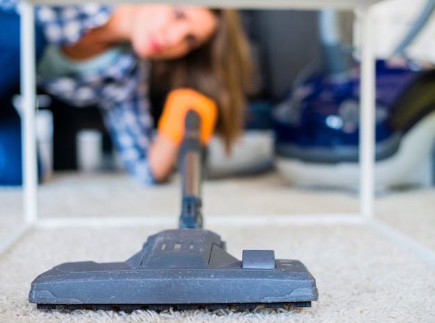 Close-up of a housemaid cleaning carpet with vacuum cleaner Free Photo