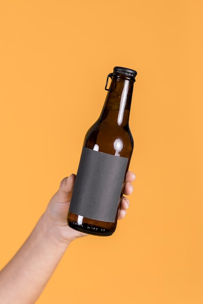 Close-up of human hand holding brown beer bottle against yellow wall backdrop Free Photo