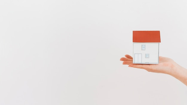 Close-up of human hand holding mini house model on white backdrop Free Photo