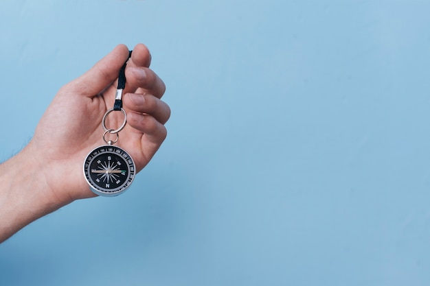 Close-up of human hand holding navigational compass on blue backdrop Free Photo