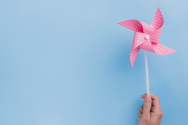 Close-up of human hand holding polka dotted pinwheel on blue backdrop Free Photo