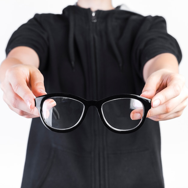 Close-up of a human hand holding spectacles Free Photo
