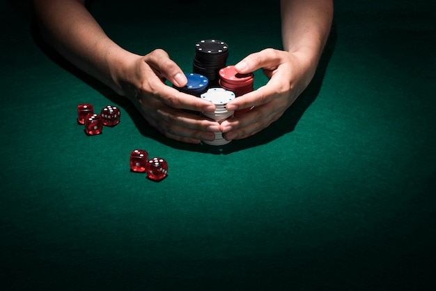 Close-up of a human hand holding stack of casino chips Free Photo
