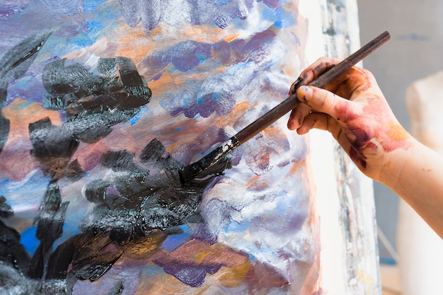 Close-up of human hand painting on canvas with paintbrush Free Photo