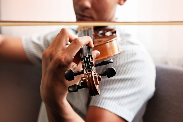 Close up human hand pressing string of violin, show how to play the instrument Premium Photo