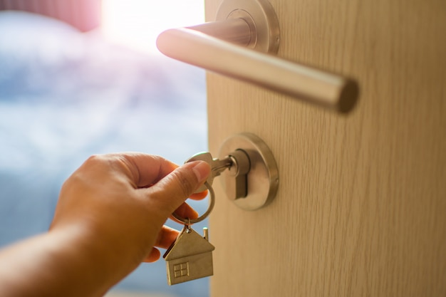 Close up human hand touch key on the door with morning light, personal loan . subject is blurry. Premium Photo