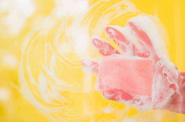 Close-up of human hand wearing pink gloves washing yellow backdrop with soap sud Free Photo
