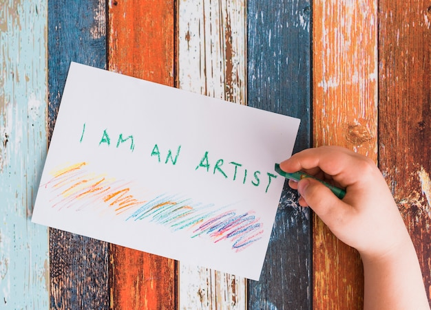 Close-up of human hand writing 'i am an artist' text on white paper with green crayon Free Photo