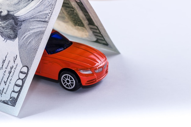 Close-up hundred dollar bill roof covers red car toy isolated on white. Premium Photo