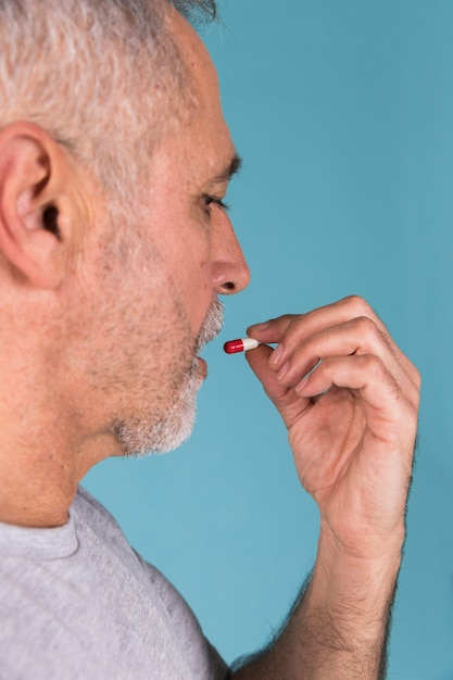 Close-up of a ill man taking capsule Free Photo