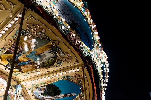 Close-up of an illuminated carousel ride under sky Free Photo