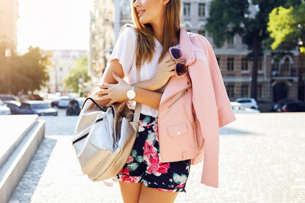Close up image of fashion details , pink jacket, stylish  shorts, sunglasses on hand,  trendy bag. pretty stylish woman in fall casual outfit walking in city. street style. Free Photo