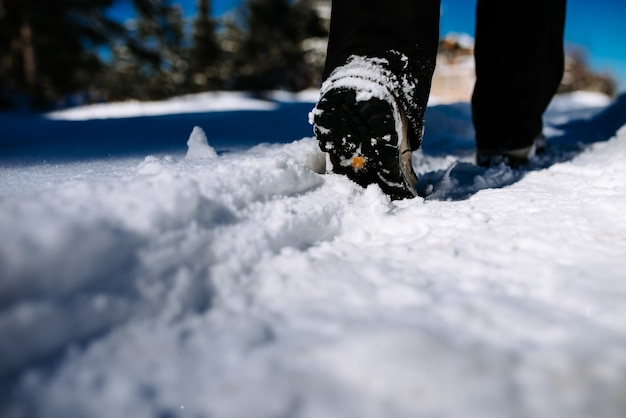 Close-up image of hiker walking on mountain covered with snow. Premium Photo