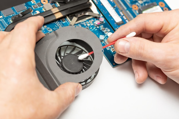 Close up image of male technician engineer hand cleaning the dust from the laptop computer fan near the circuit board with a cotton bud. Premium Photo