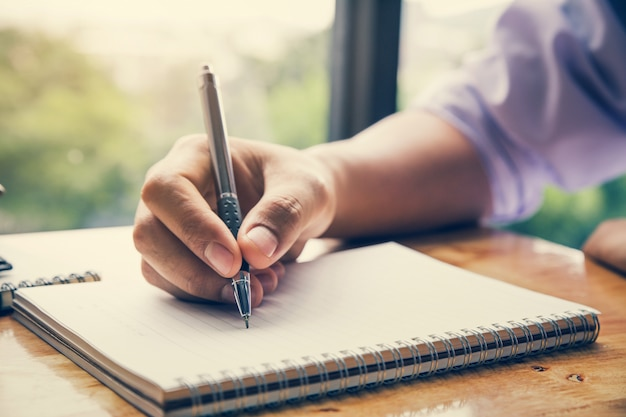 Premium Photo | Close up image of man hand writing on notebook with wooden  table background
