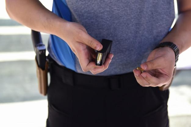 Изображение пули, вставленной в патрон при перезарядке пистолета, крупным планом Premium Фотографии