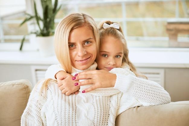 즐거운 미소로 그녀의 목에 팔을 유지하는 아름다운 젊은 어머니를 포용하는 푸른 눈의 매력적인 아기 소녀의 이미지를 닫습니다 무료 사진