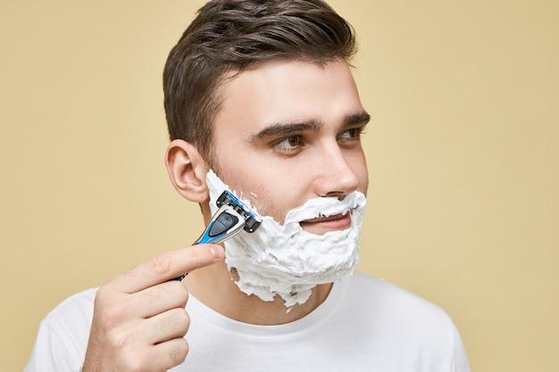 彼の髪が成長する方向にひげを剃りながら、軽く穏やかなストロークを使用してかみそりの棒を保持している格好良い若いブルネットの男性の画像をクローズアップ、表情を喜ばせ、プロセスを楽しんでいます 無料写真