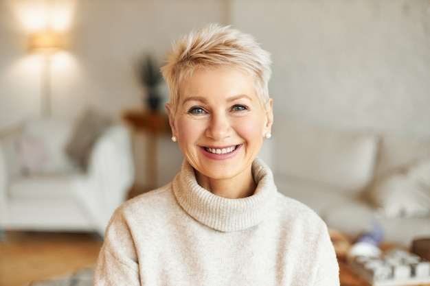 따뜻하고 아늑한 점퍼, 진주 귀걸이 및 짧은 세련된 머리를 입고 거실에 앉아 좋은 분위기에있는 행복한 좋은 찾고 우아한 50 세 여성의 이미지를 닫습니다 무료 사진