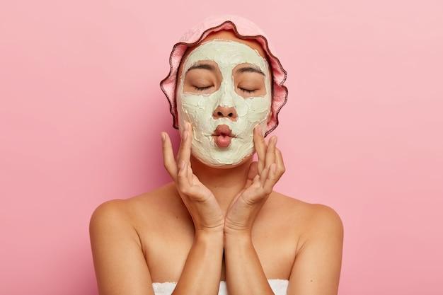 喜んでいる女性のクローズアップ画像は、乾燥肌に自家製のフェイシャルマスクを適用し、魚の口を作り、スパトリートメントを行い、裸の肩を示し、バスキャップとタオルを着用し、外観を気にし、ピンクで隔離します 無料写真