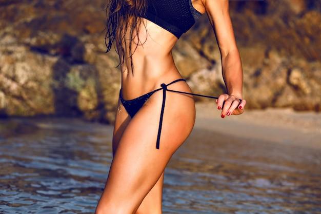 Закройте изображение сексуальной потрясающей женщины, позирующей на пляже на закате, тонированные цвета, здоровый образ жизни фитнеса. Бесплатные Фотографии