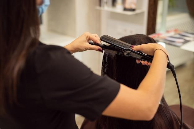 ストレートヘアアイロンを使用してヘアスタイルを作成しながら、黒い制服を着た認識できない美容師の画像をクローズアップ Premium写真