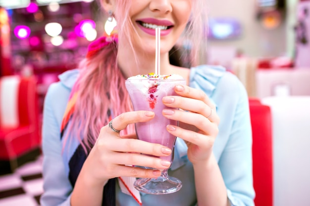 甘いイチゴのミルクセーキを保持している女性のクローズアップ画像、レトロなスタイル、パステルカラー、ヴィンテージアメリカンカフェをピンで留める 無料写真