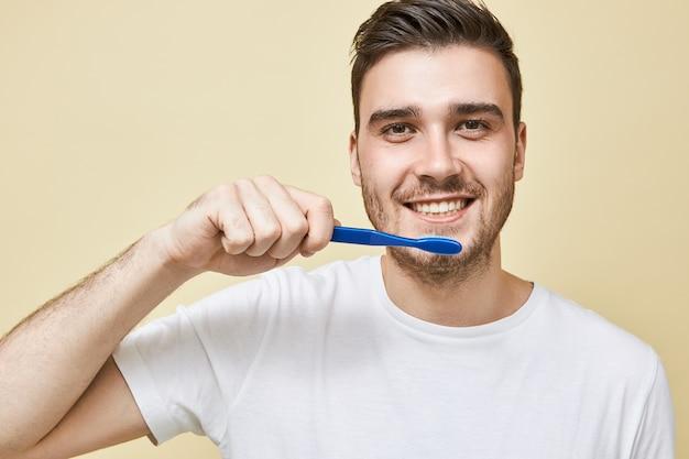 Chiudere l immagine del positivo giovane maschio con la barba lunga che tiene uno spazzolino da denti di plastica mentre si lava i denti in bagno davanti allo specchio, prendendosi cura dell'igiene dentale, avendo soddisfatto l'espressione facciale Foto Gratuite