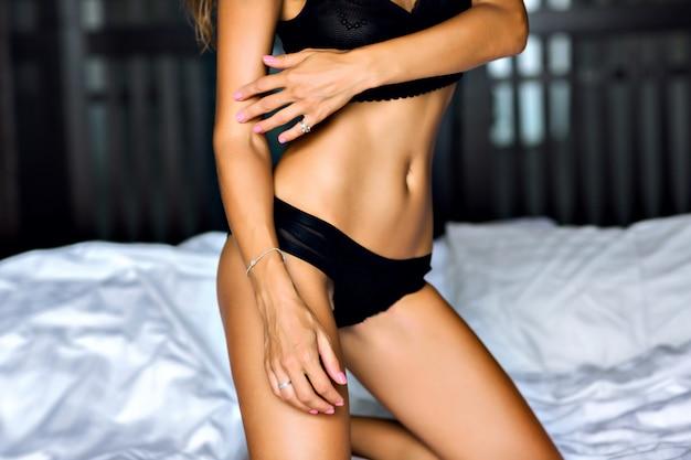 Chiuda sull'immagine della donna sexy che posa sul letto, corpo abbronzato sottile, lingerie nera, goditi il suo stile di vita mattutino, di lusso. Foto Gratuite