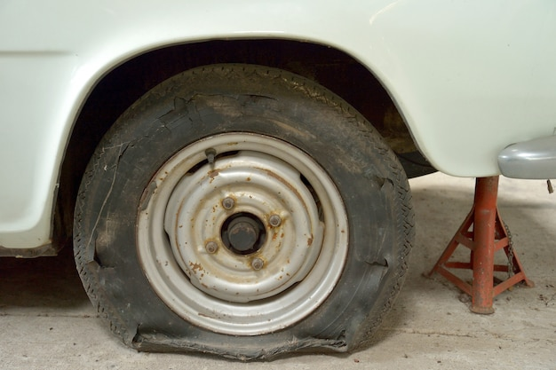 Close-up image of torn tyre on old car. Premium Photo