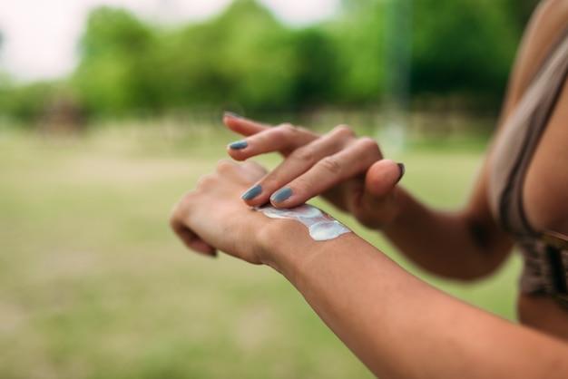 Close-up image of unrecognizable female person applying sunscreen creme. Premium Photo
