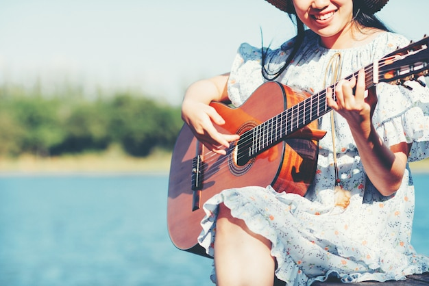 Close up images of woman's hands playing acoustic guitar Free Photo