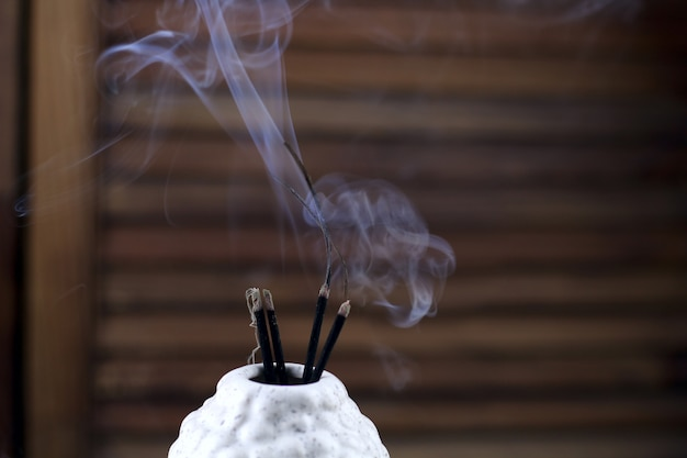 Close up of incense sticks smoke in the vase Premium Photo