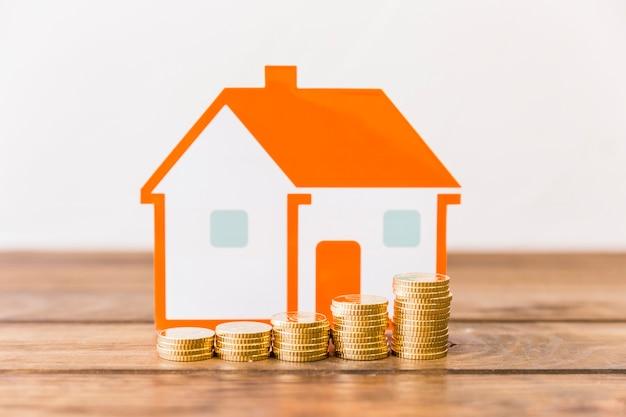 Il primo piano di aumentare le monete impilate e la casa modella sullo scrittorio di legno Foto Gratuite