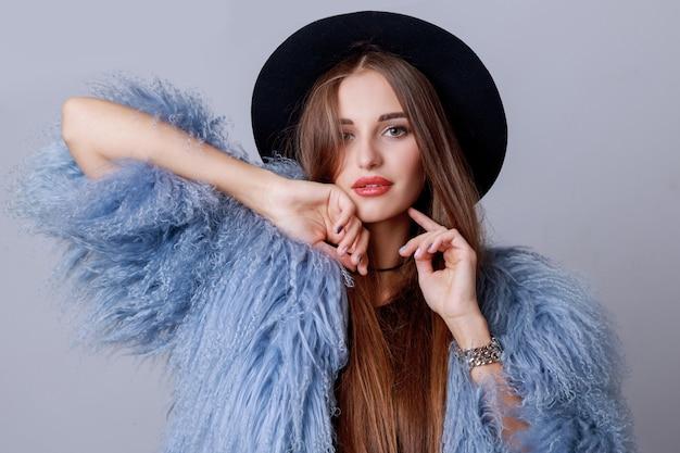 Закройте вверх по внутреннему портрету моды довольно молодой модели в стильном зимнем пушистом пальто и позировании черной шляпы. вечерний яркий макияж. Бесплатные Фотографии