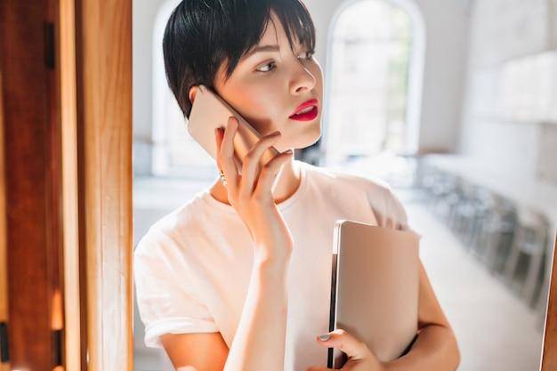 Ritratto dell'interno del primo piano della giovane donna occupata con le labbra rosse e l'acconciatura corta alla moda che parla sul telefono Foto Gratuite