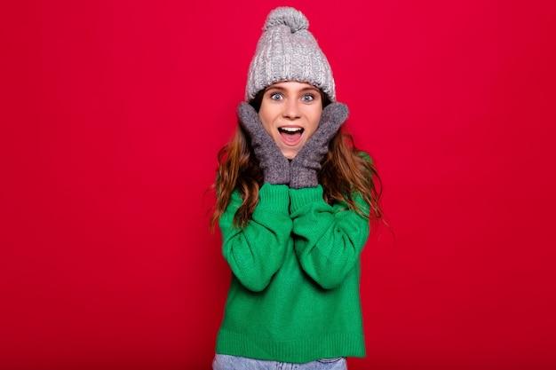 Chiuda sul ritratto dell'interno della donna graziosa alla moda efficace con berretto invernale vestito dai capelli lunghi e sweatre verde con emozioni sorprese su fondo rosso isolato Foto Gratuite