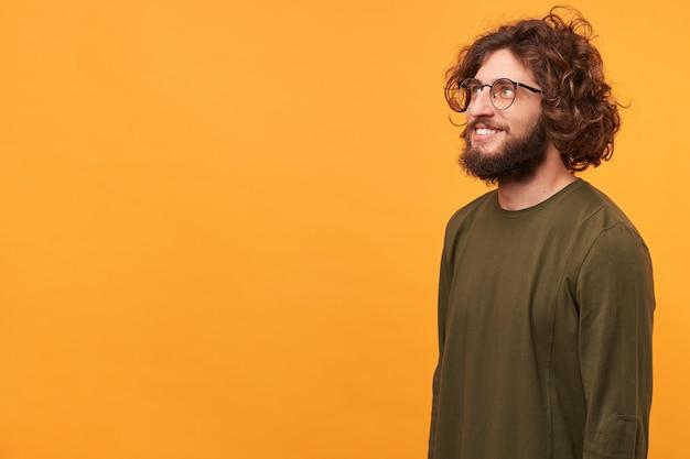 Chiuda in su del ragazzo barbuto bello felice ispirato con gli occhiali, in piedi di lato Foto Gratuite
