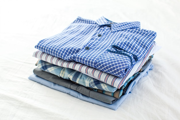 Close up of ironed and folded shirts on table at home Premium Photo