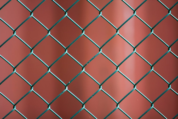 Close-up of isolated painted simple geometric black iron metal wire chain link fence eon dark red background. fence, protection and enclosure concept. Premium Photo
