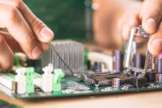 Close-up of it technician repairing cpu socket on computer motherboard Free Photo