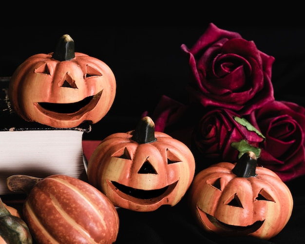 Close-up of jack-o'-lanterns and roses Free Photo