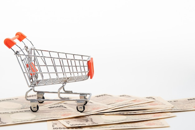 Close up japanese currency yen money banknote in small shopping trolley .   japan  economy and online market. Premium Photo